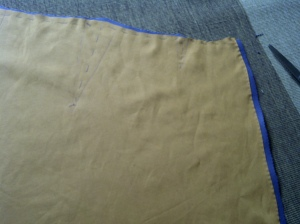 8. lining stitched to the top fabric - top stitched at the opening, and basted along the top, including the darts