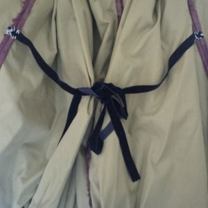 13a. tapes at the inside of the skirt, restricting the fullness to the back