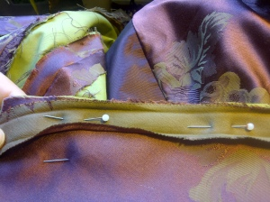 44. sewing the self fabric bias bining to the edges of the bodice)